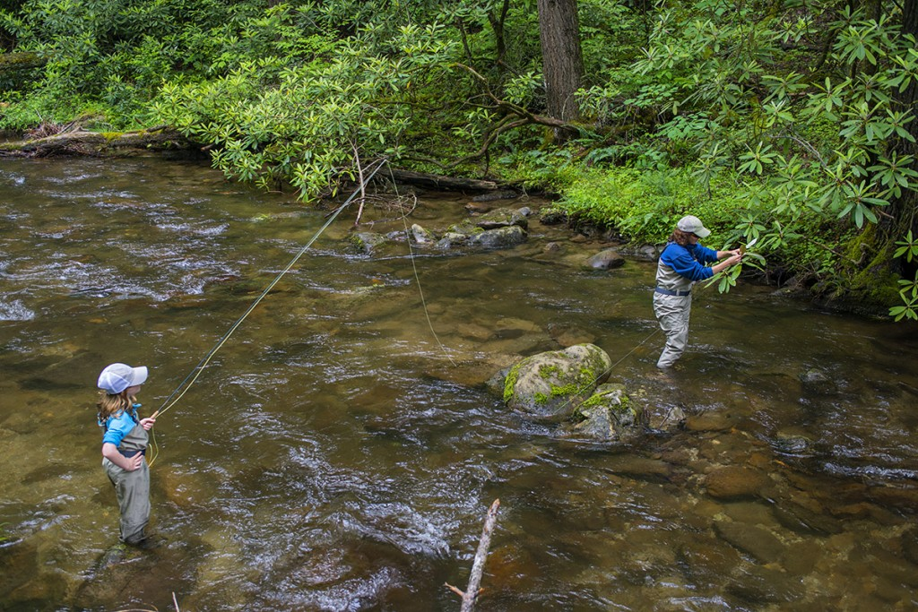 Mom pulling daughter's fly out of the trees on a Smokies creek